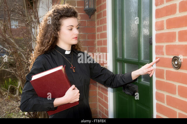 Young woman priest on a home call ringing the door bell of a house - Stock