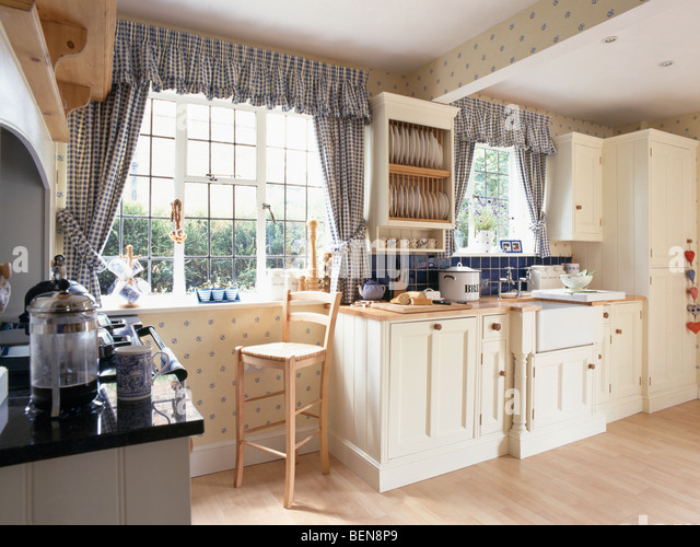 Blue Checked Curtains And Pelmets On Windows In Cream Country Kitchen With Wooden Flooring