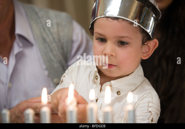 Closeup of a boy lighting Hanukkah candles family in the background. - Stock Image  sc 1 st  Alamy & Boy Lighting Hanukkah Candles Stock Photos u0026 Boy Lighting Hanukkah ... azcodes.com