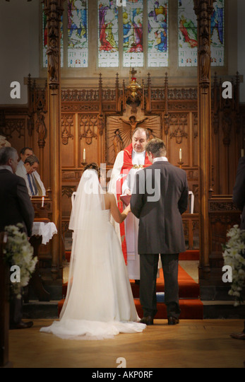 Bride And Groom Stand At The Altar Exchange Vows Rings During A Catholic Wedding Ceremony