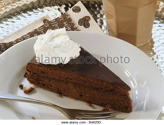 Piece of Sacher torte with cream - Stock Image