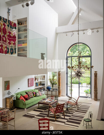 Triple-height living space with mezzanine and old textiles adding colour - Stock Image