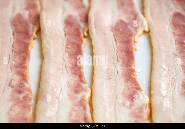 strip of fresh raw bacon close up, selective focus - Stock Image