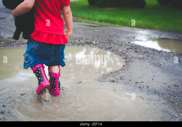 A young girl walks into a mud puddle with rain boots on wearing red and holding a small stuffed dog. - Stock Image