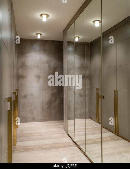 Mirrored Wardrobes In Dressing Room With Polished Concrete Walls   Stock  Image