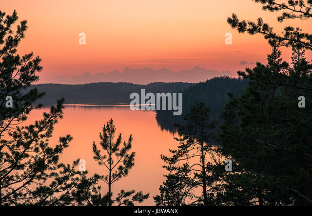 Scenic landscape with sunset and lake at summer night in Finland - Stock Image