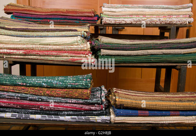 Rack of woven rag rugs ready for sale which have been woven on a loom in - Rag Rugs Stock Photos & Rag Rugs Stock Images - Alamy