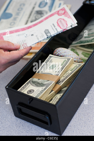 Hand inserting valuables into safe deposit box - Stock Image