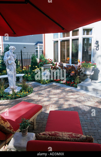 MINNEAPOLIS, MINNESOTA TOWNHOME PATIO GARDEN WITH STATUE OF PAN TERME,  HADDENSTONE BENCH, CANNA