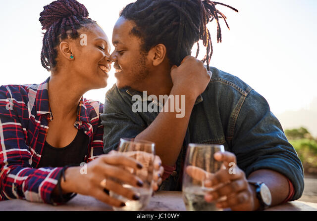 Real couple of african descent about to kiss while embracing - Stock Image