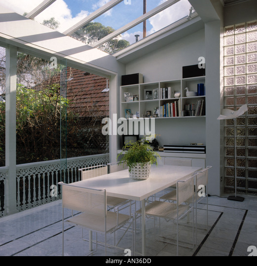 White Table And Chairs In Modern Dining Room Extension With Glass Roof Walls