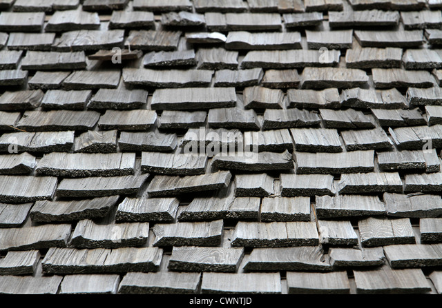 Close Up Of A Worn Shake Shingle Roof Showing Warped, Weathered Shingles.