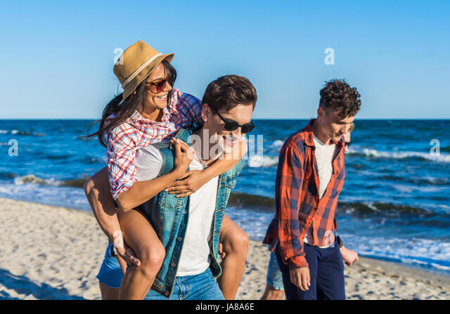 young funny couple in sunglasses piggybacking on the beach. - Stock Image