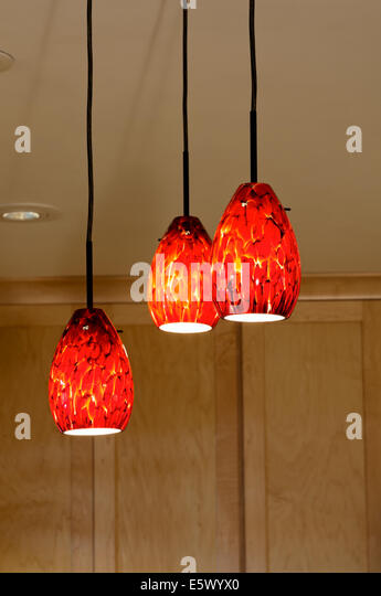 Decorative glass pendant lights hanging from kitchen ceiling and maple  cabinets behind them - Stock Image