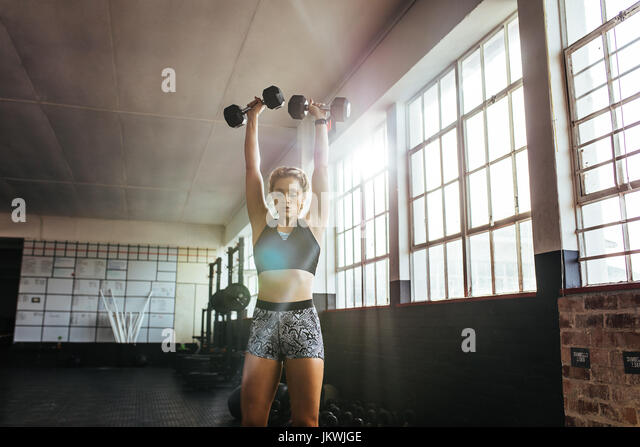 Athlete excercising with dumbbells for muscle and strength building. Young woman lifting dumbbells at the gym . - Stock Image