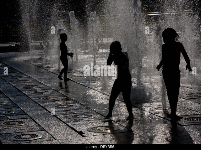 Silhouettes Of Children Playing In Water Fountains