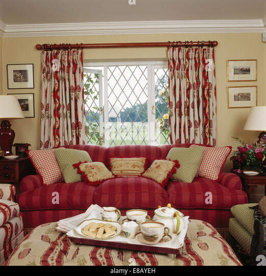 Tea Tray On Stool In Front Of Red Sofa And Lattice Window With Patterned  Curtains In