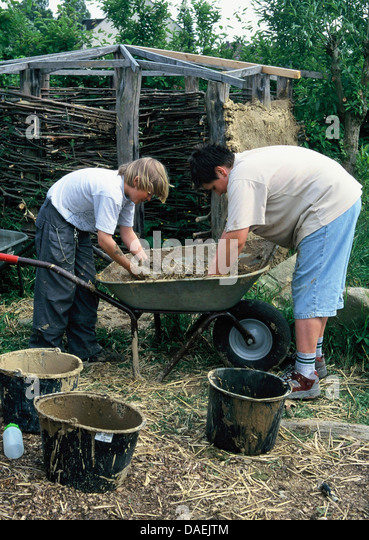 Awesome Two Boys Building A Clay Hut In The Garden, Germany   Stock Image