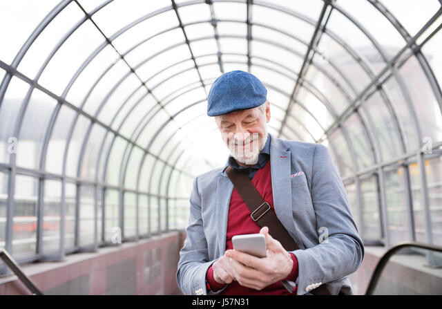 Senior man with smartphone against glass ceiling texting. - Stock Image