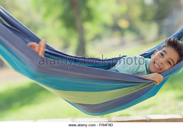 young boy with a big smile as he swings in hammock   stock image boy in a hammock stock photos  u0026 boy in a hammock stock images   alamy  rh   alamy