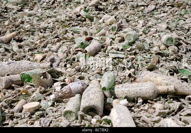 Bottles broken in public recycling materials - Stock Image