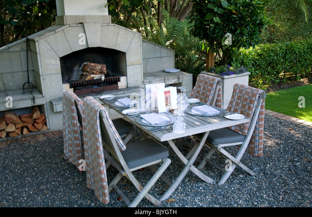 A Table Is Set For Four Diners In Front Of An Outdoor Fireplace The Summer