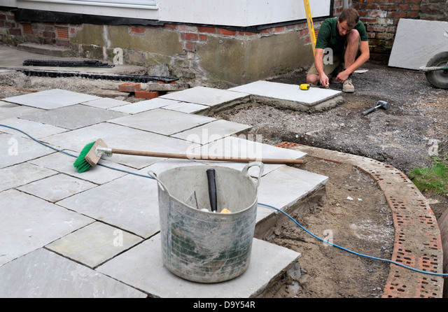 Laying Natural Stone : Laying a patio stock photos images