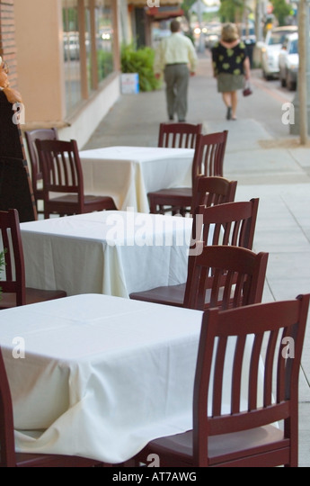 White Tablecloths Adorn Tables At A Sidewalk Cafe In Orange County,  California As Tourists Walk