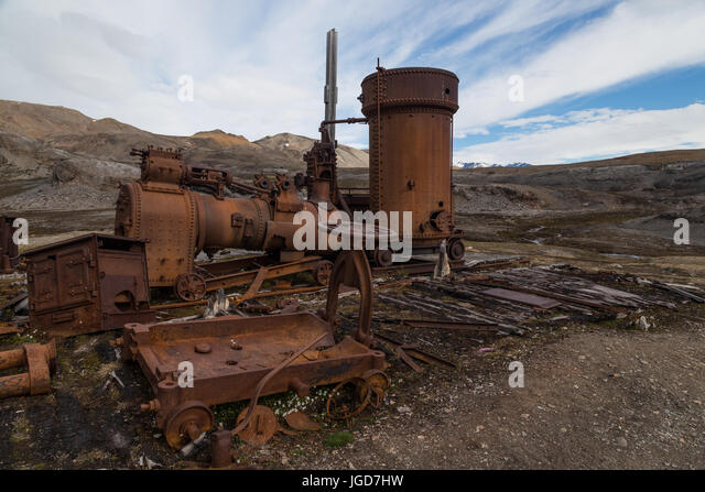 The rusting remains of a large steam engine remain in position above the wooden foundations of an abandoned hut - Stock Image