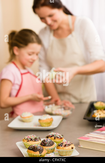 Woman Decorating Cupcakes young woman baking cupcakes stock photos & young woman baking
