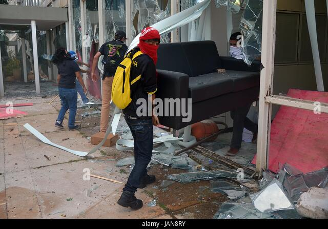 Anti-government rioters loot furniture from a government ministry building during demonstrations by trade unions - Stock Image