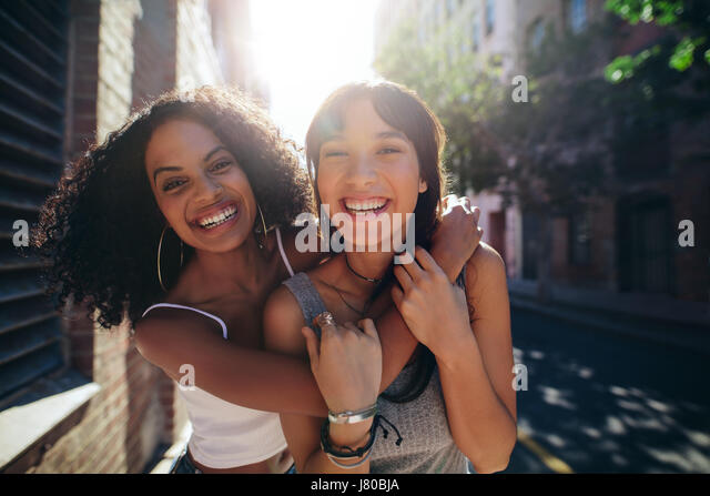 Portrait of two young women on city street having fun. Female friends on road embracing and smiling outdoors. - Stock Image