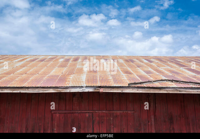 High Quality Building With Rusty Tin Roof With Clouds Overhead.   Stock Image