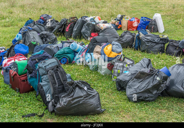 Personal possessions, rucksacks and bin liners of clothes of camping holiday group. Possible use as metaphor for - Stock Image