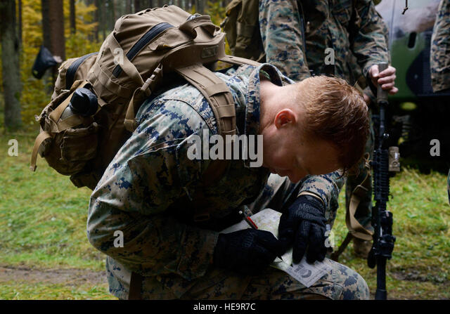 A U S Marine Plots Points On A Map As Part Of The Land Navigation Challenge As