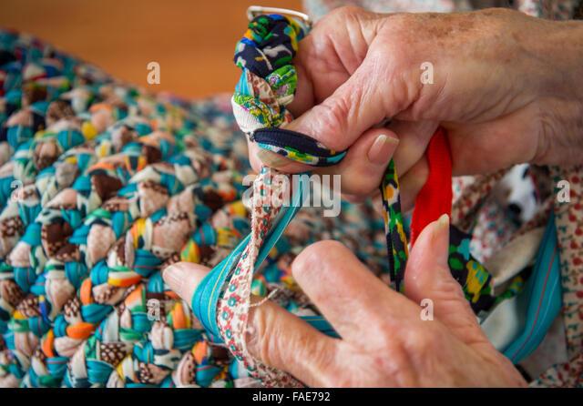 Elderly Woman Braiding A Rug.   Stock Image