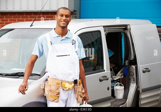 decorator wearing overalls standing next to van stock image - Decorator