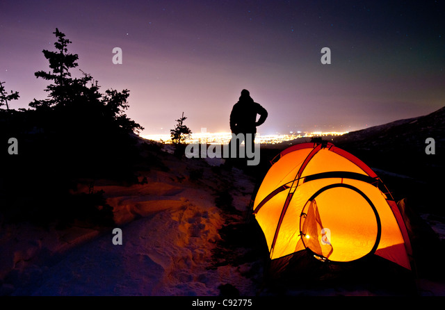 Silhouette of a man standing by a candlelit tent in Chugach State Park with the city & Tent City Stock Photos u0026 Tent City Stock Images - Alamy