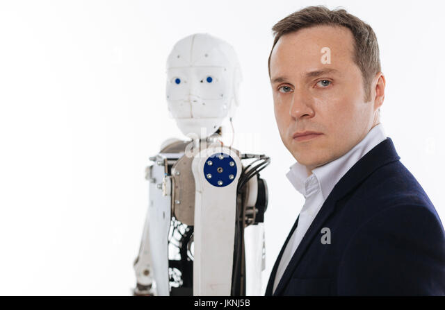Progressive inventor and his robot standing in the same poses - Stock Image