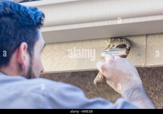 painter using a brush to paint house fascia under rain gutter stock image - Gutter Brush