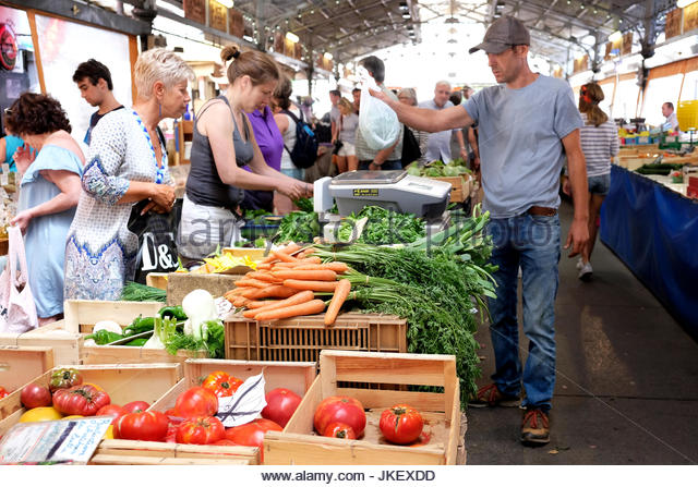 A customer buys fresh fruit and vegetables from a fresh produce stall in antibes market, France. Her goods are handed - Stock Image