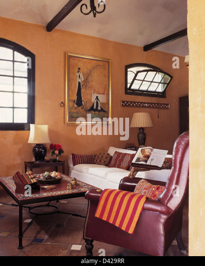 Leather Chair And Tiled Top Table In Spanish Living Room With Painting On  Wall Above White