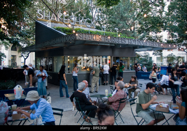 People sit at tables around a restaurant kiosk in madison square park