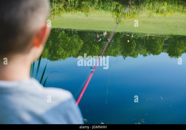 A child fishing at a pond in a rural area. - Stock Image