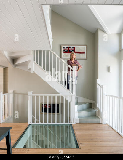 Glass floor on first storey landing with framed old british flags along the staircase. The walls are painted in - Stock Image