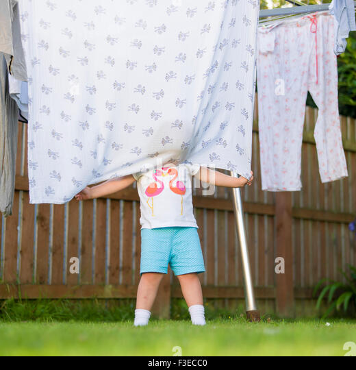 3 year old hiding behind blanket on washing line in garden stock image - Hidden Pictures For 3 Year Olds
