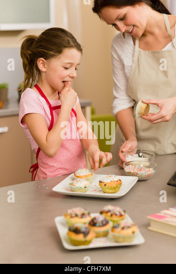 little girl taste sprinkles decorating cupcakes with mother at home stock image