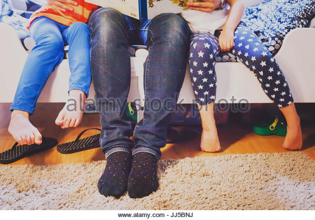 father at home with two kids sitting together and reading book, legs of family - Stock Image