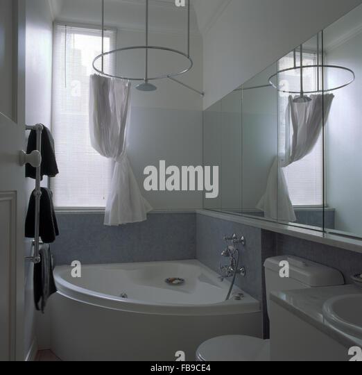 White Drapes On Circular Shower Rail Above Corner Bath In Nineties Bathroom
