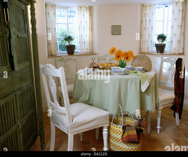 loose covers on dining chairs at table with pale green cloth in dining